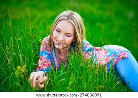 Beautiful Spring Young Woman Outdoors Enjoying Nature. Healthy Smiling Girl in Green Grass. Spring Meadow. Beautiful Lady Lying on the field - stock photo