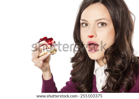 Beautiful stained girl has been caught while eating cake - stock photo