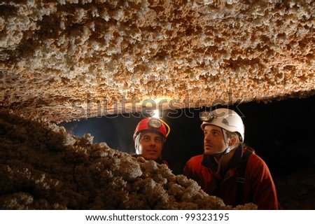 Beautiful stalactites in a cave with two speleologist explorers - stock photo