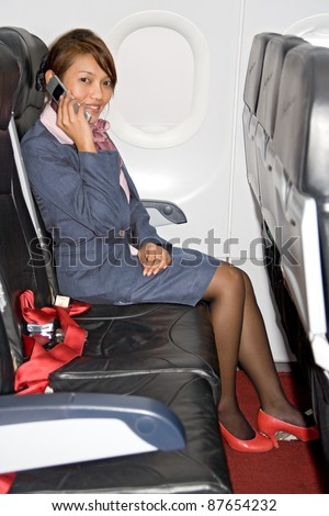 Beautiful stewardess calls from airplanes. Asian woman in a business suit sitting on a plane and calling from phone. Hostess on the plane with mobile phone. Business woman sitting on plane with phone.