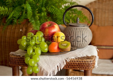 Beautiful still life image of fruits and teapot in the interior with wicker furniture - stock photo