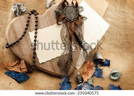Beautiful still life of big wooden heart and few retro items on a sackcloth background. - stock photo