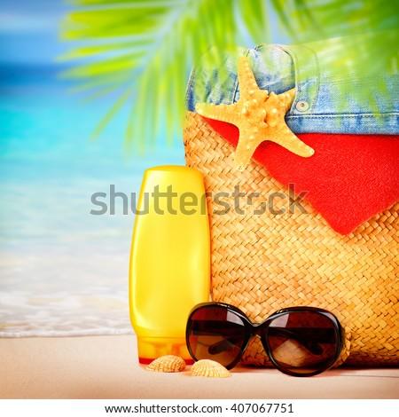 Beautiful still life of women's beach items on sandy seashore, tropical vacation, summer holidays concept - stock photo