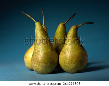 Beautiful still life with pears on a blue background. Studio photography. Beautiful poster for interior design. - stock photo