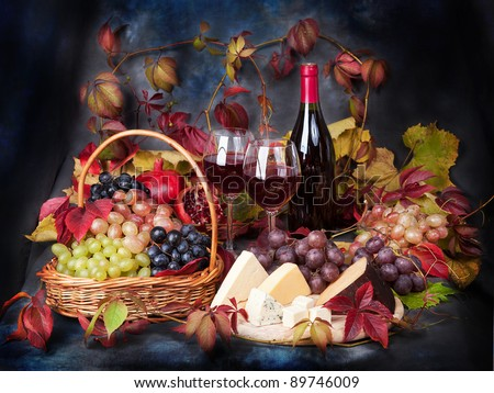 Beautiful still life with wine glasses, grapes, pomegranate and cheese