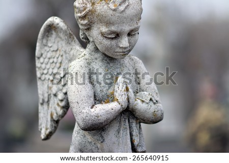 Beautiful stone statue of praying angel - stock photo