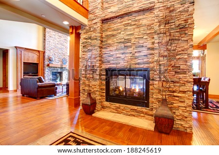 Beautiful stone wall with built-in fake fireplace. Two vases with dry branches complete the wall look - stock photo