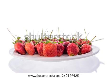 Beautiful strawberries on  white plate - stock photo