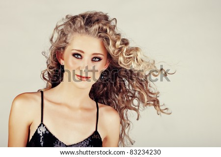 beautiful strawberry blond happy teenage girl with green eyes and long curly hair blowing in wind over grey studio background . - stock photo