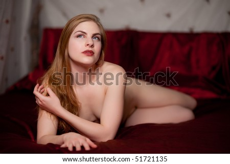 Beautiful strawberry blond woman on red satin sheets. Shallow depth of field.