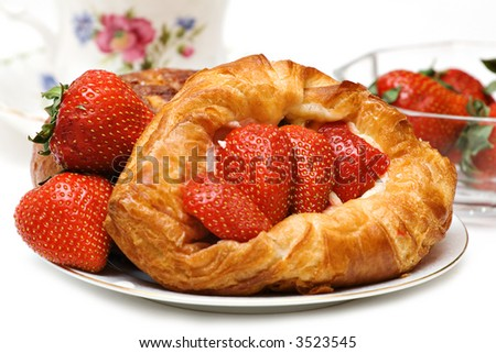 Beautiful Strawberry pastry with fresh fruit and a cup of tea.