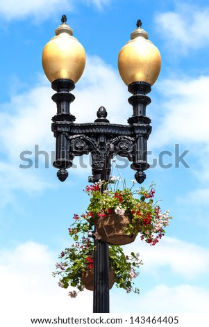 Beautiful street lamps with hanging flower baskets. Close up against a blue sky with white clouds.