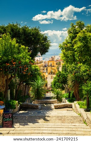 beautiful street with descending steps and orange trees in Taormina, Sicily - stock photo