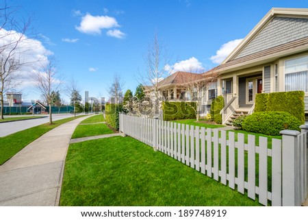 Beautiful street with houses against blue sky  in Vancouver, Canada. - stock photo