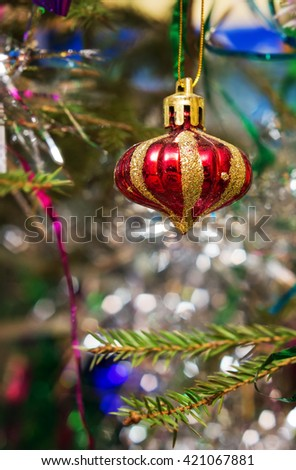 Beautiful striped Christmas ball on the tree branches. - stock photo