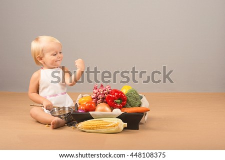 Beautiful strong blond toddler sitting on the floor and is considering various vegetables in a basket: corn, red and yellow peppers, onions, tomatoes, carrots, broccoli - stock photo