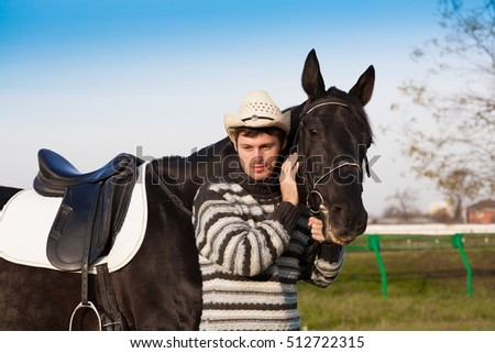 Beautiful strong man cowboy nearby black horse. Has happy  smile face, striped pullover, hat. Has sport body. Portrait nature. People and animals. Equestrian. Close up.