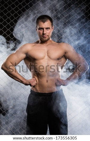 Beautiful, strong man on fence background