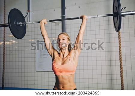 Beautiful strong young woman with barbell and weight plates overhead. Fit young female athlete lifting heavy weights. Caucasian female model performing crossfit exercise. - stock photo