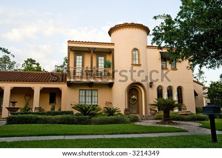 beautiful stucco Mediterranean-styled home with lush landscaping - stock photo