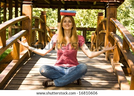 Beautiful student balanced with two books on head in yoga lotus pose in natural environment.