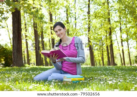 beautiful student enjoying with book in nature, smiling and looking at camera - stock photo