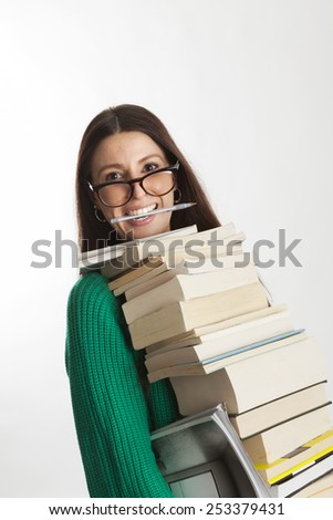 Beautiful student female with glasses holding many books and smiling with a pen in her mouth. Going to study or working in a library - bookshop. Gray background. - stock photo
