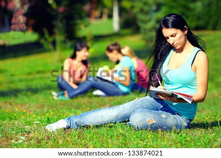 beautiful student girl on colorful sunny lawn - stock photo