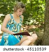 Beautiful student girl reading book  in park - stock photo
