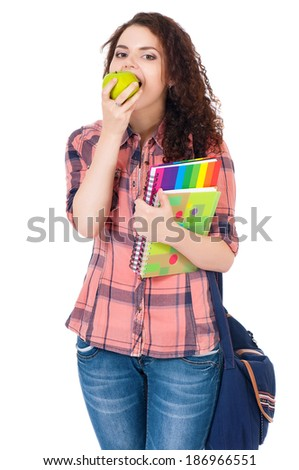 Beautiful student girl with bag, exercise books and green apple, isolated on white background