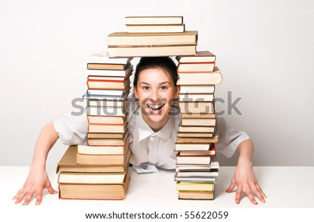 Beautiful student girl with happy smile between books - stock photo