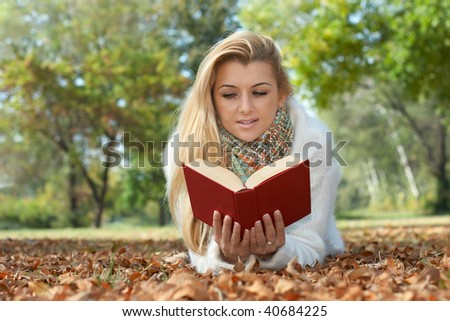Beautiful student reading book in the park. - stock photo