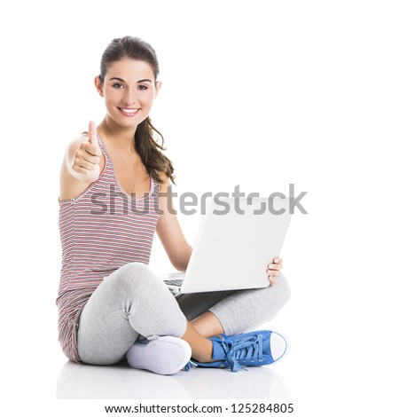Beautiful student sitting in the floor with a laptop and thumbs up, isolated in white - stock photo