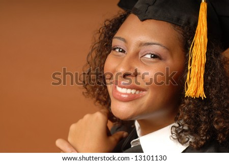 Beautiful student smiling while in her graduation cap and gown - stock photo