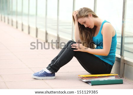 Beautiful student teenager girl depressed sitting on the floor outdoor  - stock photo