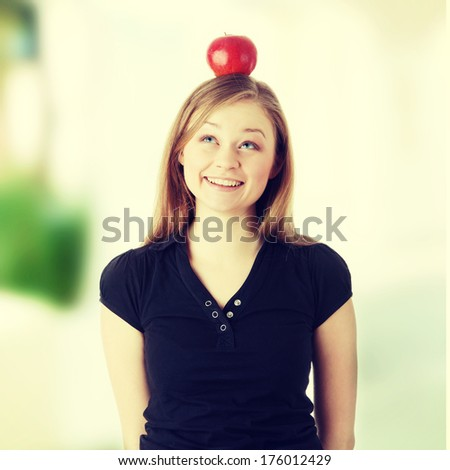 Beautiful student woman have apple on her head - learning concept - stock photo