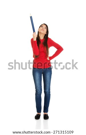 Beautiful student woman pointing up with a big pencil. - stock photo
