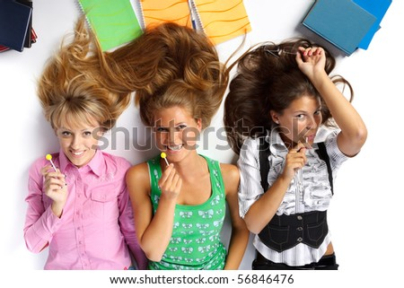 Beautiful students lay on a floor with sugar candies and writing-books on a white background. Break time - stock photo