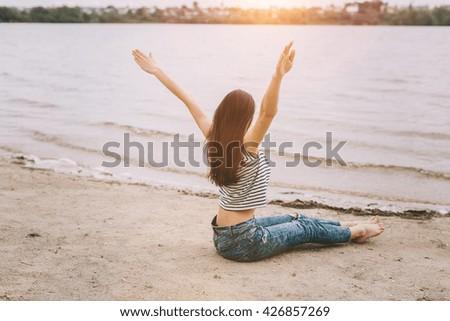 Beautiful stylish and fashionable girl yoga on the beach. - stock photo