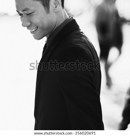 Beautiful stylish Asian groom walking on the summer streets of Venice, Italy