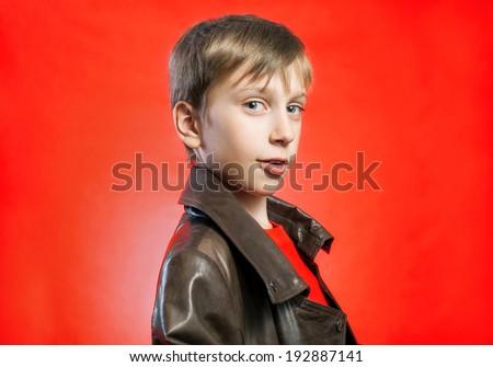 Beautiful stylish blond boy wearing leather coat posing over red background  - stock photo