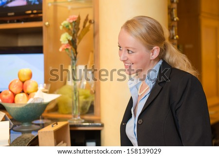 Beautiful stylish blond hotel receptionist standing behind the service desk in a hotel lobby looking at the camera with a friendly smile - stock photo