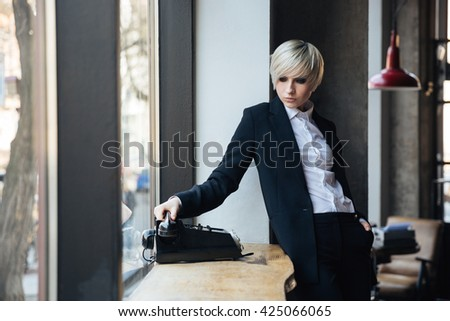 Beautiful stylish blonde girl talking on the phone in cafe - stock photo