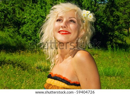 Beautiful stylish blonde in a meadow - stock photo
