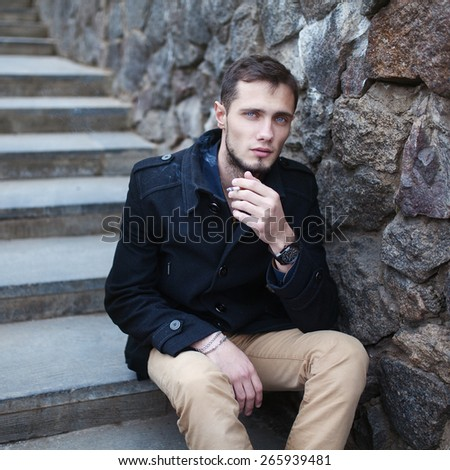 beautiful stylish brutal bearded guy man smokes a cigarette while sitting on the stairs near a stone wall - stock photo