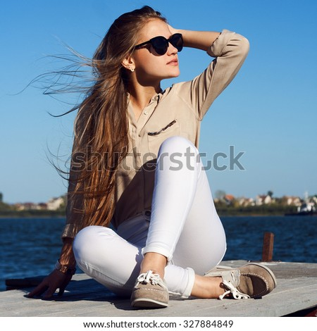 Beautiful stylish confident young woman sitting on a pier and looking away . Trendy outfit black sunglasses white jeans and casual blouse - stock photo