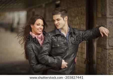 beautiful stylish couple dressed in leather jackets under bridge - stock photo