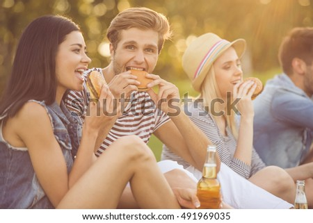 Beautiful stylish friends are drinking cocktails, eating sandwiches, communicating and smiling while resting in the park