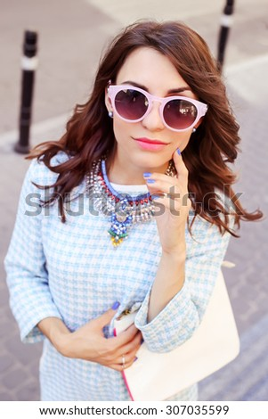Beautiful stylish girl. Brunette wearing sunglasses. Street portrait, street fashion. Stylish brown-haired woman in the street. Checked dress. Girl with clutch.