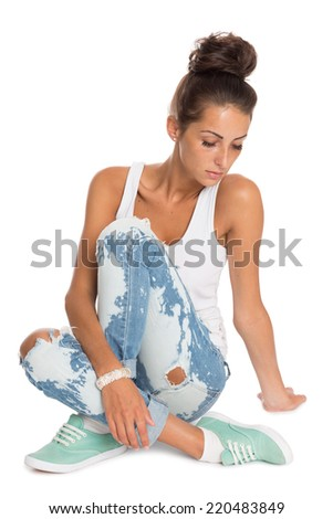 Beautiful stylish girl in a blue ripped jeans sitting on the floor. - stock photo